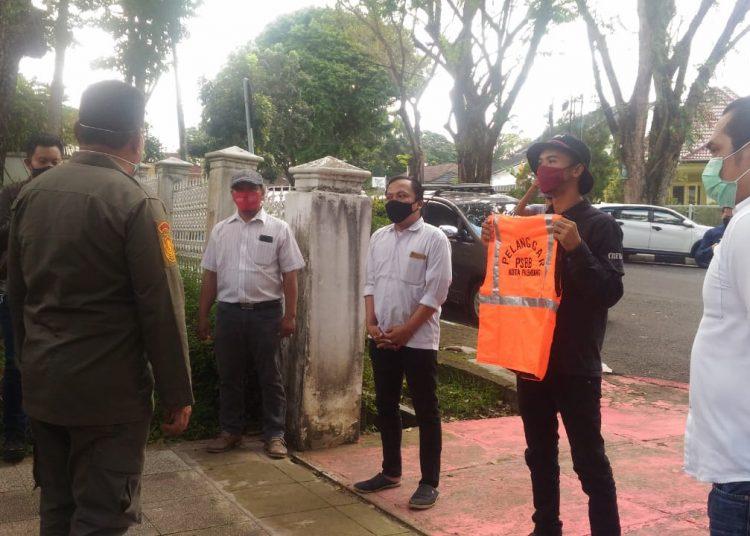Relawan COVID-19 di Palembang saat menyerahkan secara simbolis kepada gugus tugas rompu oren sebagai hadiah untuk Wali Kota Palembang yang diduga melakukan pelanggaran PSBB. Foto: Istimewa