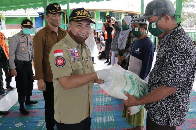 Sekda Muba Apriyadi menyerahkan bantuan Pemkab Muba kepada warga Trans SP I dan SP II Desa Air Balui, Kecamatan Sanga Desa, Senin (01/06). (fornews.co/humas pemkab muba)