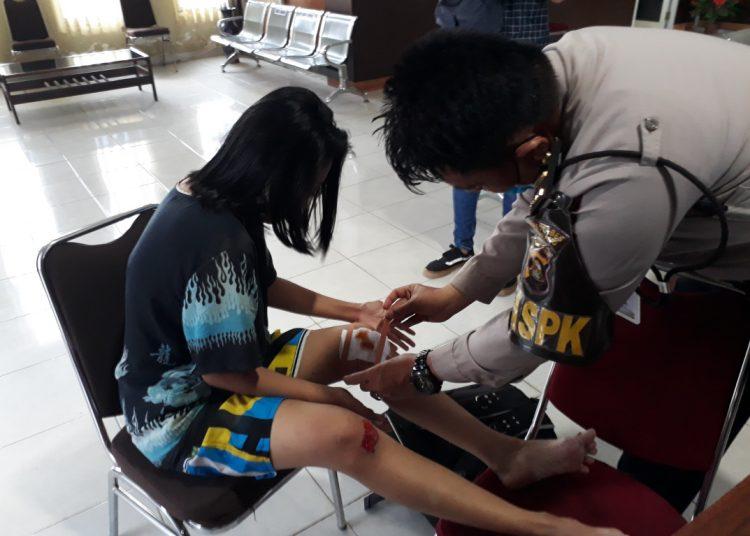 Petugas piket SPKT Polrestabes Palembang mengobati luka Diana yang menjadi korban penjambretan saat melapor ke Polrestabes Palembang, Senin (01/06). (fornews.co/rusli gumay)