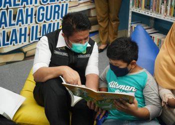 Gubernur Sumsel Herman Deru menemani seorang anak membaca buku pada peresmian Pojok Baca Digital (Pocadi) Sungai Ijuk yang berada di Kelurahan Keramasan, Kecamatan Kertapati, Kamis (21/1/2021). (fornews.co/humas provinsi sumsel)