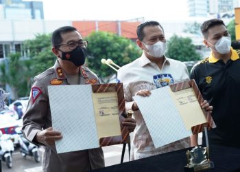 Kepala Korlantas Polri Irjen Istiono dan Ketua Umum IMI Bambang Soesatyo menunjukkan surat hibah 10 motor listrik di halaman gedung NTMC Polri, Jakarta Selatan, Senin (3/5/2021). (fornews.co/humas polri)