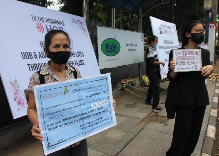 Sejumlah aktivis melakukan aksi teaterikal dan mengirimkan karangan bunga untuk sindikasi perbankan pemberi pinjaman dan ADRO, Senin (3/5). (istimewa)