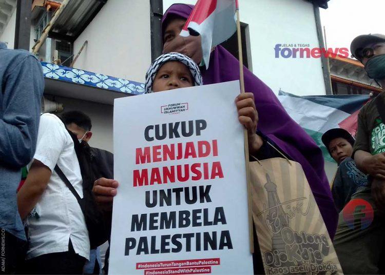 SEORANG ibu dan anak membentang poster dan bendera kecil turut dalam aksi damai dukung Palestina di Titik Nol Kilometer Kota Yogyakarta pada Jum'at (21/5/2021). (foto fornews.co/adam)