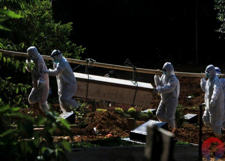 Petugas pemakaman dan mobil membawa peti jenazah yang akan dimakamkan di TPU khusus pemakaman jenazah COVID-19 Gandus Hill, Palembang, Kamis (29/7/2021). (fornews.co/mushaful imam)