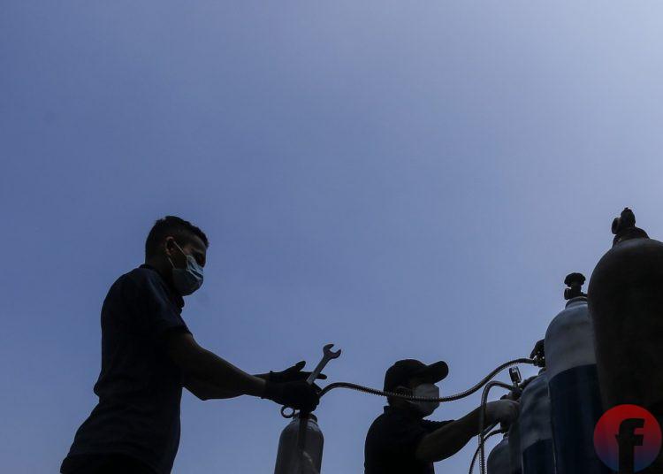 Petugas sedang mengisikan oksigen, di Lapangan Golf Komplek PT Pusri Palembang, Sabtu (31/7/2021). (fornews.co/mushaful imam)