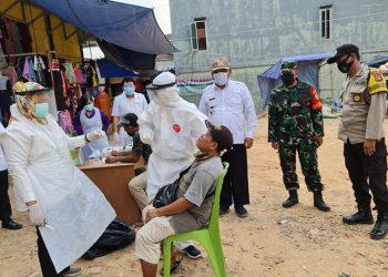 Petugas lagi melakukan swab kepada salah satu pedagang di Pasar Randik, Sekayu, Kamis (5/8/2021). (fornews.co/humas pemkab muba)