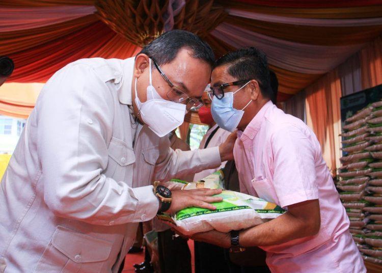 Bupati Muba, Dodi Reza Alex, saat menyerahkan bantuan beras kepada salah satu warga Muba yang berdomisili di Palembang, di Kantor Perwakilan Muba Palembang, Senin (6/9/2021). (fornews.co/humas pemkab muba)