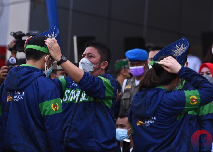 Gubernur Sumsel, Herman Deru, memasang tanjak kepada atlet yang akan berangkat mengikuti PON XX Papua, di Plaza Stadion Gelora Sriwijaya Jakabaring Palembang, Rabu (15/9/2021). (fornews.co/mushaful imam)
