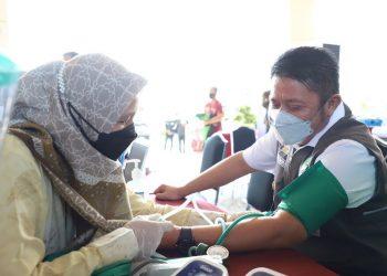 Gubernur Sumsel, Herman Deru, tengah memeriksa tensi darah di sela-sela pemberian vaksinasi untuk driver ojek online di Politeknik Pariwisata (Poltekpar) Palembang, Kamis (9/9/2021). (fornews.co/humas pemprov sumsel)