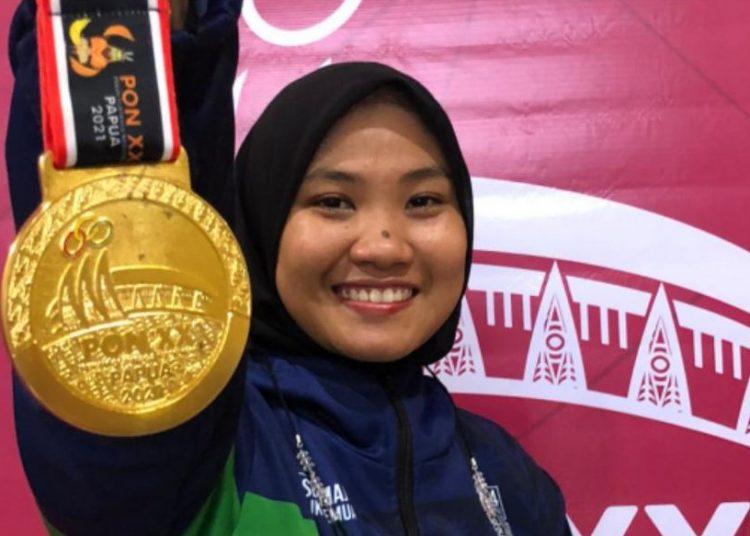 Atlet Pencak Silat Sumsel, Fransiska Sandra Dewi, memamerkan keping medali emas kelas tanding F 70-75 kg putri, pada final di venue silat GOR Toware, Sentani, Papua, Selasa (12/10/2021). (fornews.co/ist)