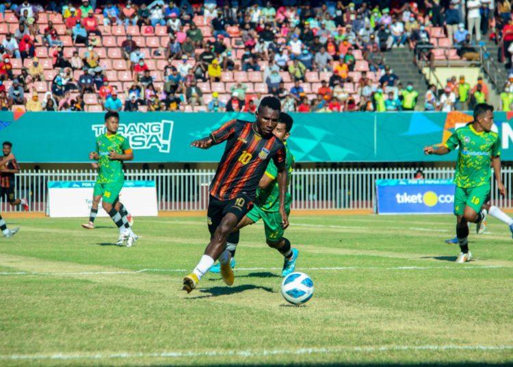 Pemain Papua, Ricky Ricardo Cawor dibayangi pemain Kalimantan Timur pada semifinal sepakbola PON XX Papua, di Stadion Mandala, Jayapura, Selasa (12/10/2021) (fornews.co/Foto: PB PON XX PAPUA/ Zani Renfaan)